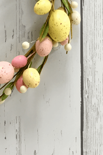 White painted wood background with Easter egg vine wreath