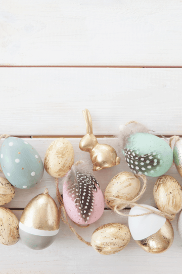 Picture of farmhouse Easter decor ideas like painted wood gold and pastel Easter eggs with feathers and bunnies