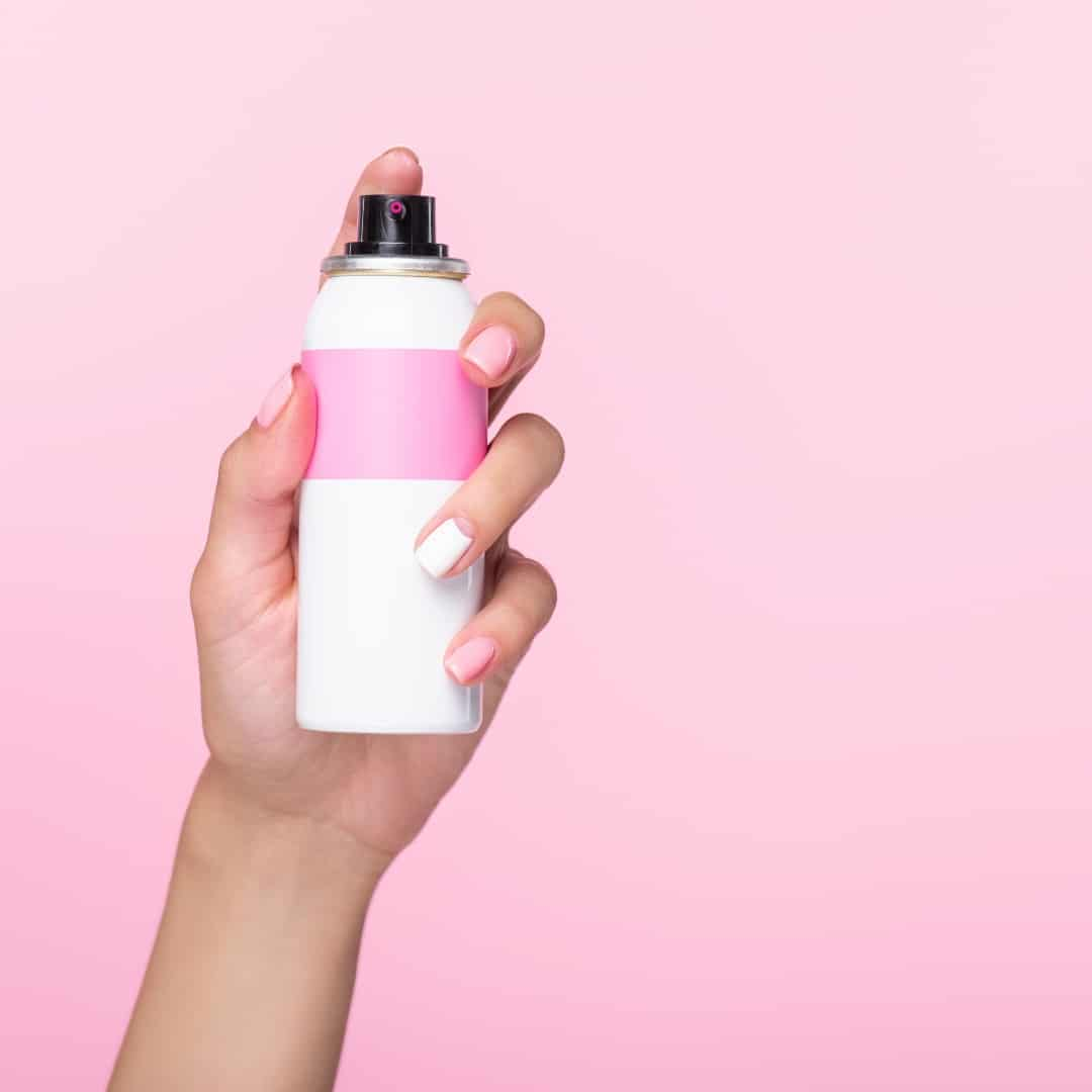 Genius Hairspray Removal Hack (pink background with hand holding hairspray can)