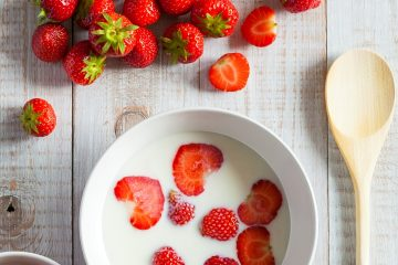 Strawberries on table and in bowl of cream with wooden spoon