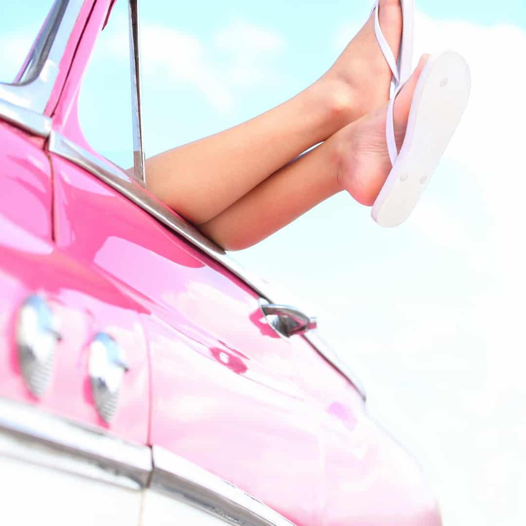 Pink convertible car with legs sticking out with white flip flops on